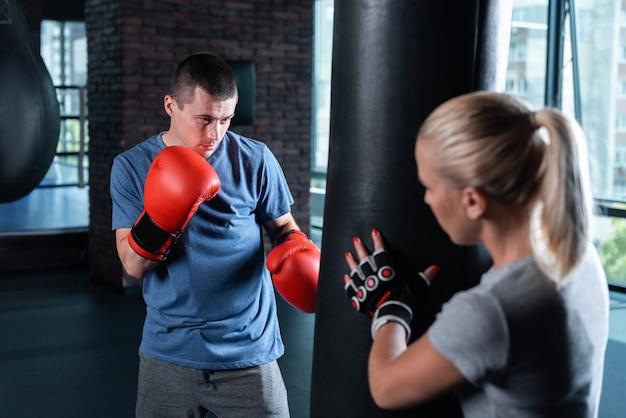Camisa azul. boxeador profissional de cabelos escuros e camisa esporte azul, trabalhando com seu treinador