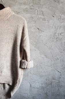 Camisa bege quente de manga longa com cabide preto pendurado no fundo cinza