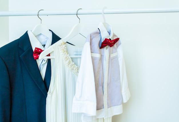 Camisa branca clássica masculina com uma gravata borboleta vermelha e um terno em um cabide