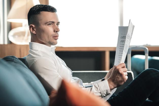 Camisa branca. homem bonito de cabelos escuros, camisa branca, segurando o jornal, lendo o noticiário da manhã