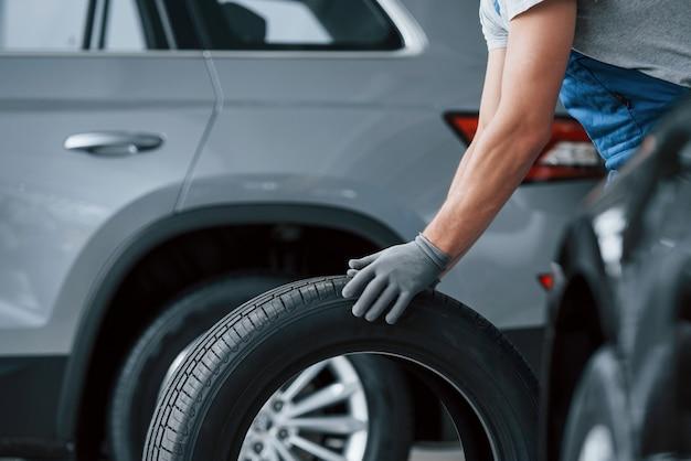 Camisa cinza. mecânico segurando um pneu na oficina. substituição de pneus de inverno e verão.