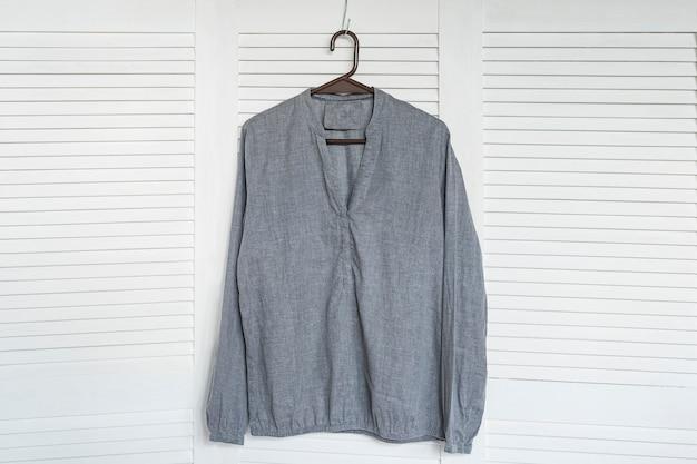 Camisa cinza pendurada em um cabide.