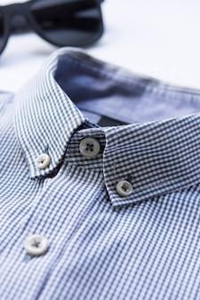 Camisa colarinho azul escuro e óculos escuros no fundo isolado