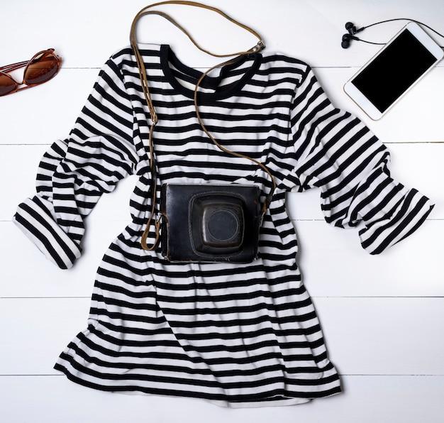 Camisa de algodão branco em listras pretas e uma câmera velha do vintage