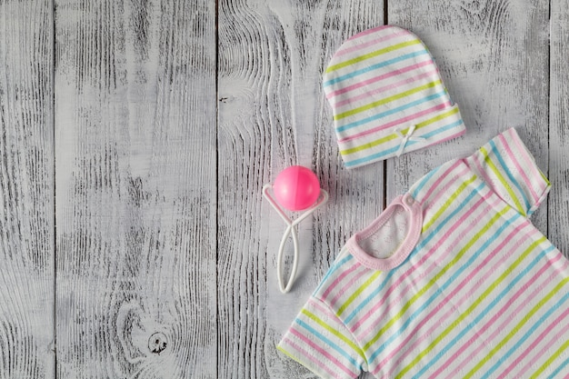 Camisa de bebê na área de trabalho de madeira. brincar
