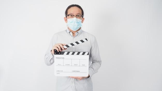 Camisa de desgaste masculino e máscara facial e claquete de mão segura ou placa de filme. é usado na produção de vídeo e na indústria do cinema em fundo branco.