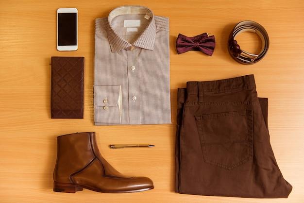 Camisa de homem, calças, gravata borboleta, cinto, sapatos e telefone celular.