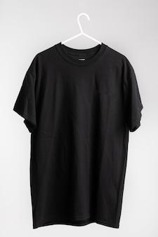 Camisa de manga curta em cabide de pano com parede branca no fundo