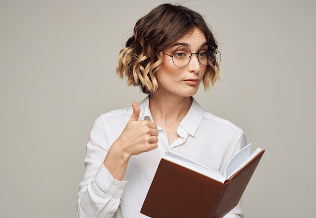 Camisa de mulher de negócios de cabelo curto branco e bloco de notas na mão