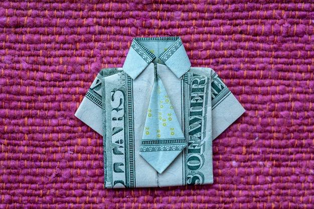 Camisa de origami feita de notas de dólar em fundo de tecido vermelho. fechar-se. camiseta nota de dólar