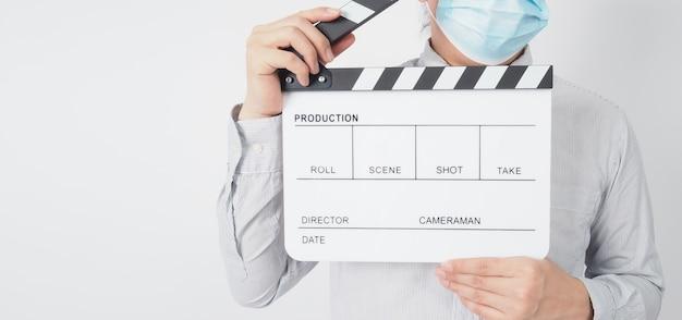 Camisa de vestir masculina e máscara facial e claquete de retenção de mão ou quadro de filme em fundo branco