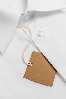 Camisa dobrada com arranjo de etiqueta de papelão em branco