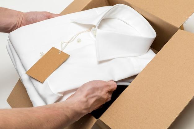 Camisa dobrada de ângulo alto com composição de etiqueta de papelão em branco