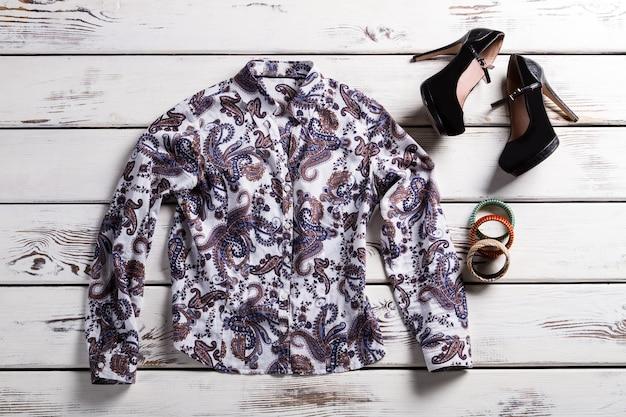 Camisa floral e sapatos de mulher. roupas da moda em fundo de madeira. camisa de desenho popular. sapatos de salto fosco e camisa.