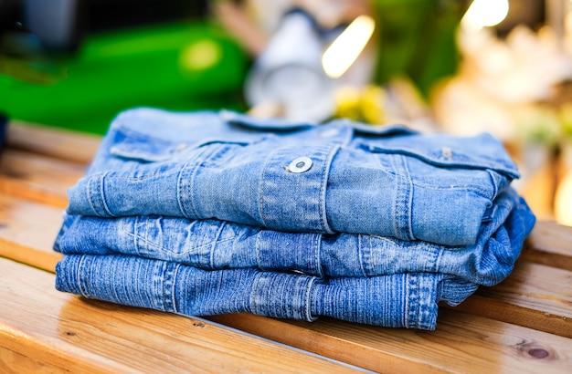 Camisa jeans. camisas de ganga enroladas estão sobre o balcão da loja.