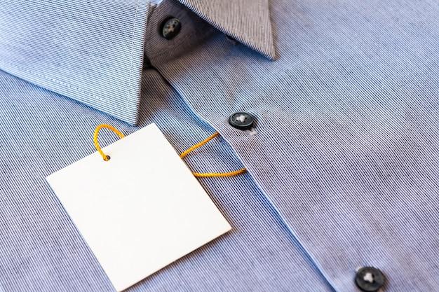 Camisa masculina de listras cinza pequenas com etiqueta de preço e cordão amarelo-laranja