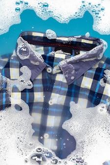 Camisa mergulhe na dissolução de detergente em pó. conceito de roupa