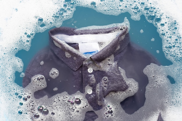 Camisa polo cinza mergulhe na dissolução da água com detergente em pó. conceito de lavanderia