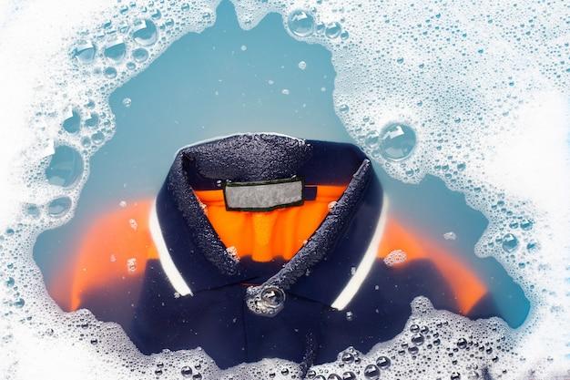 Camisa polo mergulhar em dissolução de água detergente em pó. conceito de roupa