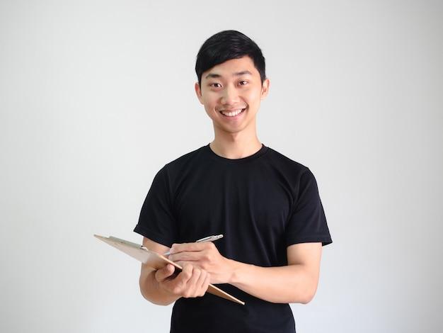 Camisa preta de jovem segurando uma prancheta de madeira e uma caneta prateada na mão e um retrato de sorriso feliz
