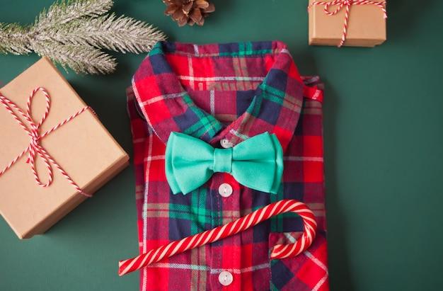 Camisa quadriculada vermelha, borboleta de gravata, pirulito, caixas de presente e decoração de natal no verde. véspera de ano novo. moda de natal.
