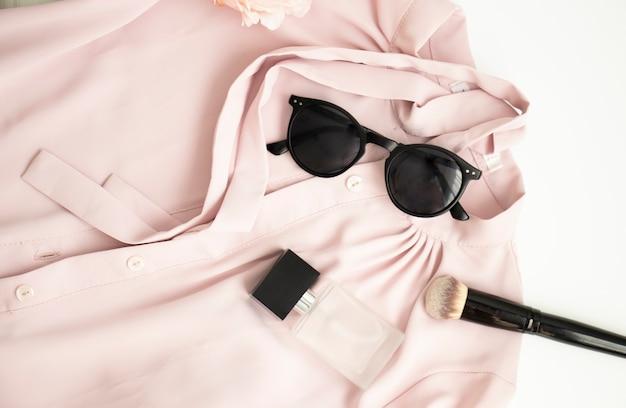 Camisa rosa feminina flatlay, óculos de sol, frasco com perfume, acessórios em pele rosa