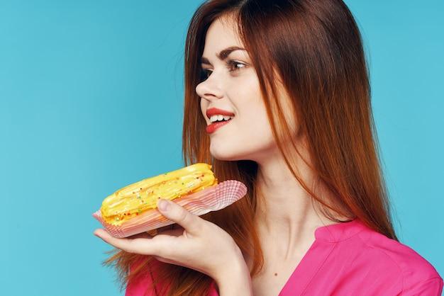 Camisa rosa mulher glamorosa com éclairs nas mãos de doces