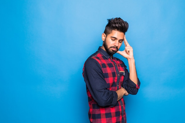 Camisa vestindo do homem indiano novo com mão no queixo que pensa sobre a pergunta, expressão pensativa que está sobre o espaço azul isolado. sorrindo com cara de pensativo. conceito de dúvida.