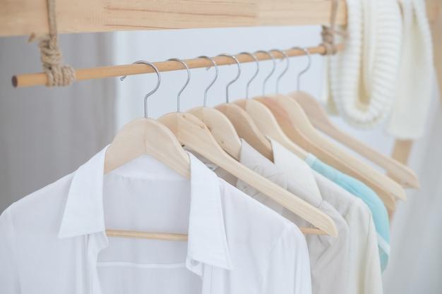Camisas brancas penduradas em prateleiras de pano interno branco
