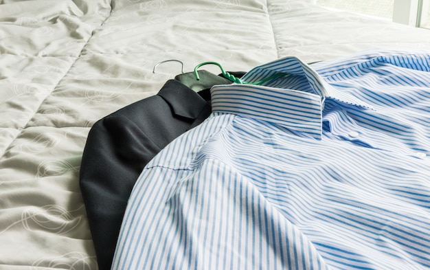 Camisas clássicas masculinas e terno na cama