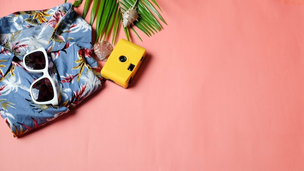 Camisas da câmera do viajante dos acessórios e folha de palmeira dos óculos de sol no fundo e no copyspace cor-de-rosa. vista superior conceito verão.