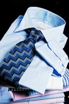 Camisas dobradas com gravata sobre o fundo preto. Foto Premium