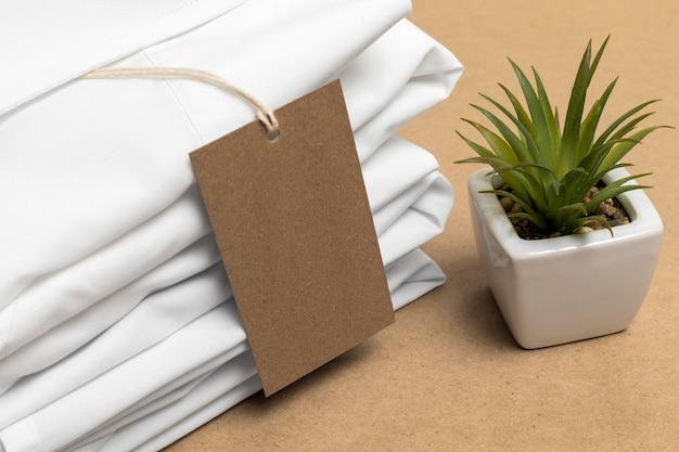 Camisas dobradas com variedade de etiquetas de papelão em branco ao lado de uma planta