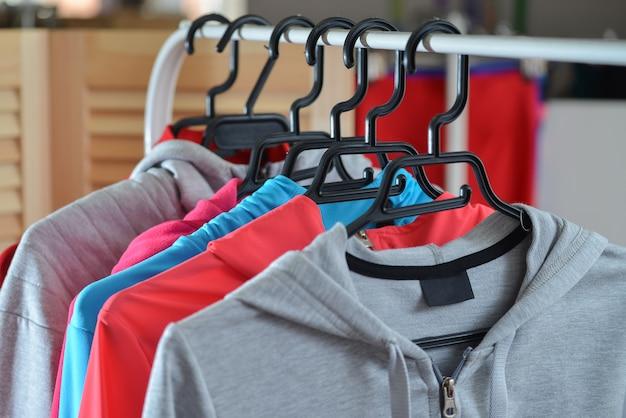 Camisas esportivas coloridas e jaquetas penduradas no cabideiro em uma loja de moda