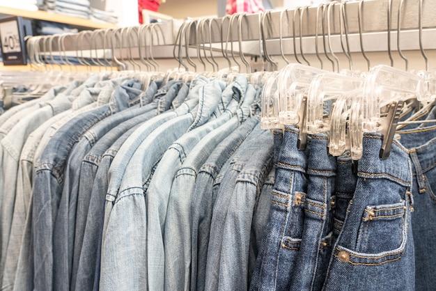Camisas masculinas das calças de brim dos homens classificadas em ganchos de roupa em um trilho do armário do vestuário da loja