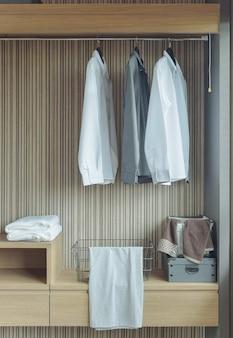 Camisas penduradas no guarda-roupa de madeira