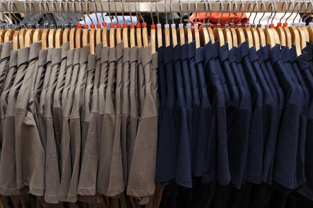 Camisas polo masculinas de diferentes tamanhos em cabides.
