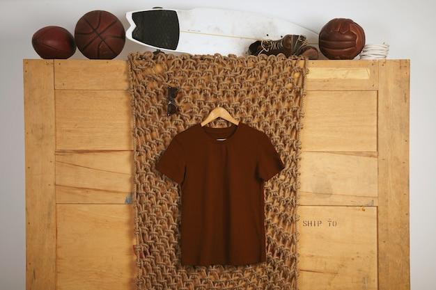 Camiseta básica de algodão marrom apresentada em interior rústico com bolas de couro vintage no topo