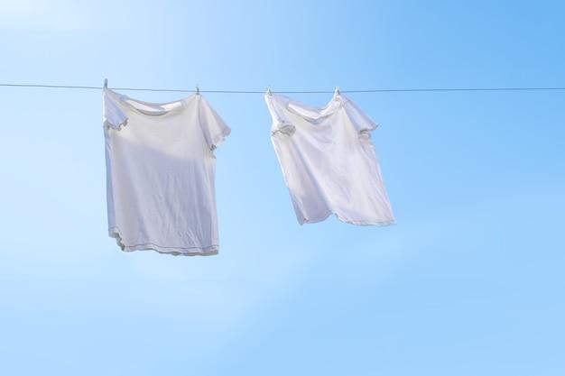 Camiseta branca no varal contra o céu azul