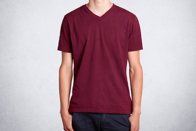 Camiseta casual vermelha escura, apresentada em branco. peça de algodão, usada no jovem esbelto e alto, desempenhando o papel de modelo. empresa de pessoas, roupas e publicidade.