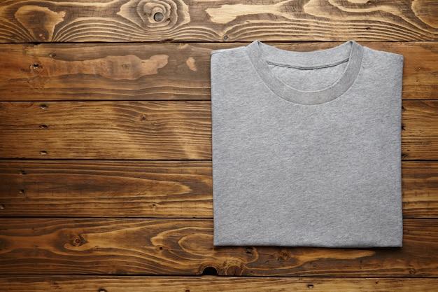 Camiseta cinza em branco dobrada com precisão na vista de cima de uma mesa de madeira rústica