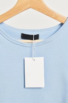 Camiseta com uma maquete de etiqueta em branco em um cabide de madeira