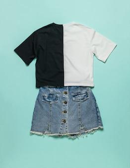 Camiseta de dois tons e saia jeans em uma superfície azul