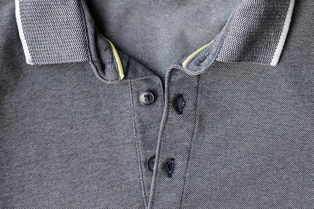 Camiseta de malha de algodão com gola aberta e botões de textura cinza polo fundo