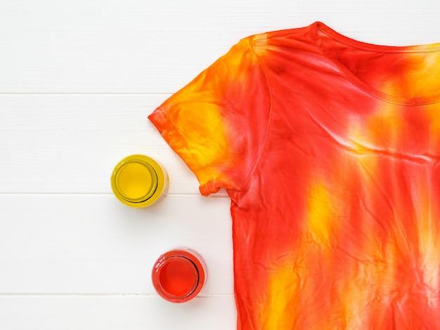 Camiseta decorada em estilo tie dye e potes de tinta em uma mesa branca