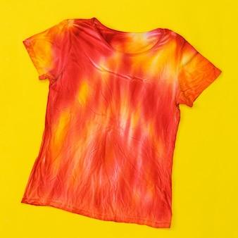 Camiseta decorada em estilo tie dye nas cores amarelo e vermelho. postura plana. tecido tingido em estilo tie dye. postura plana.
