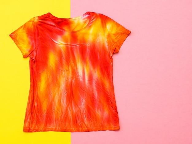 Camiseta decorada em estilo tie dye nas cores amarelo e vermelho sobre uma superfície amarela e rosa