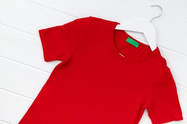 Camiseta feminina com vista plana de cima no cabide na superfície branca