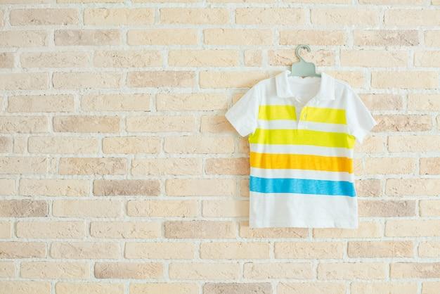 Camiseta infantil com listras no cabide na parede