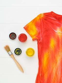 Camiseta no estilo tie dye, tinta e pincel em uma mesa branca